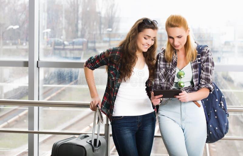 Dwa dziewczyn stojak z walizkami przy lotniskiem i patrzeć pastylkę Wycieczka z przyjaciółmi obraz royalty free
