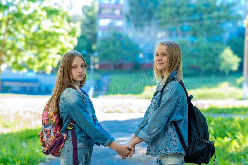 Dwa dziewczyn uczennica Trzyma each s ` inne ręki Za plecakiem Odzież cajgi odziewają Pojęcie jest lepszy niż fotografia royalty free