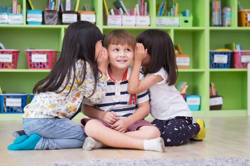 Dwa dziewczyna dzieciaka szepczą sekret przy ucho chłopiec w bibliotece przy dziecina preschool, zabawą i szczęśliwymi dziećmi, z obraz royalty free