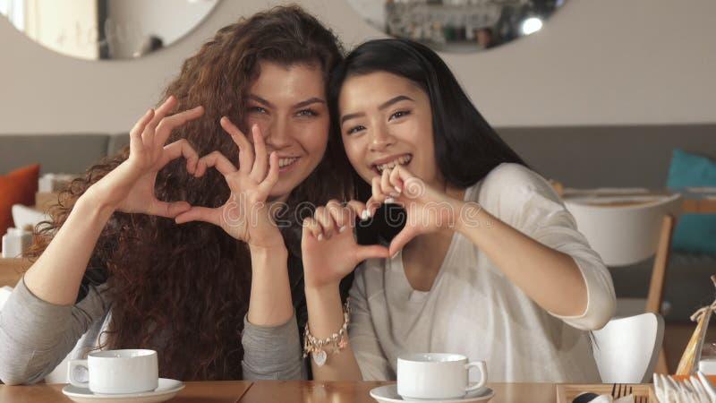 Dwa dziewczyna gesta serca przy kawiarnią obrazy stock