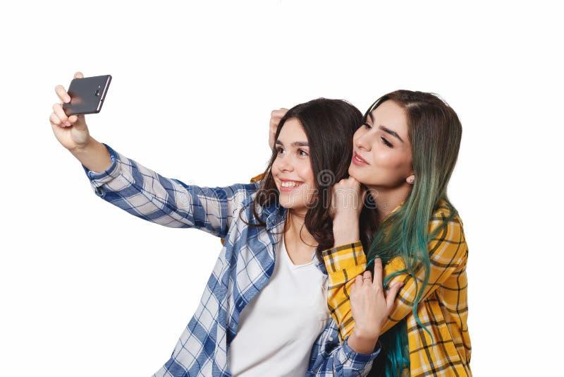 Dwa dziewczyna przyjaciela bierze selfie z smartphone, odizolowywającym na białym tle fotografia royalty free