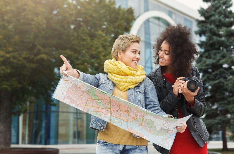 Dwa dziewczyna przyjaciela outdoors z papierową miasto mapą fotografia stock