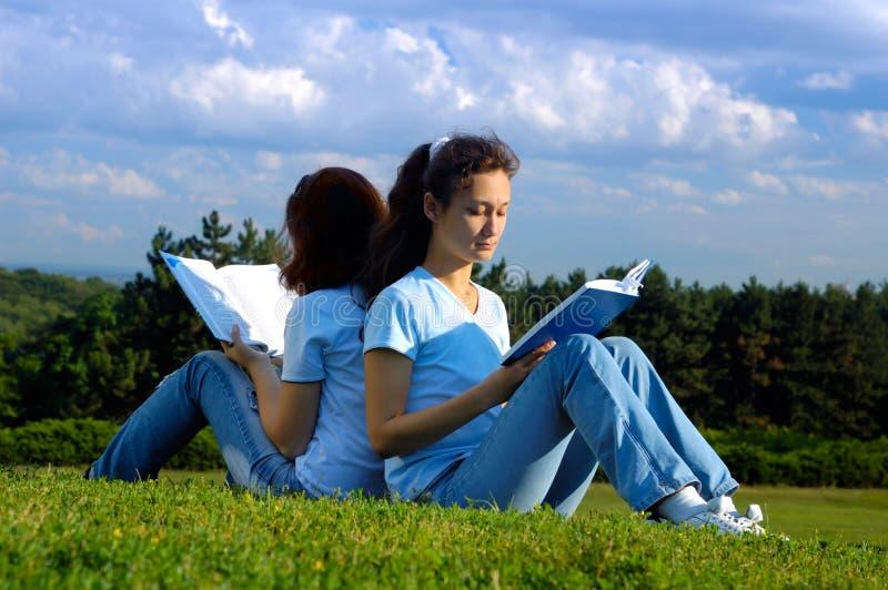Dwa dziewczyna ucznia studiuje czytać outdoors obraz royalty free