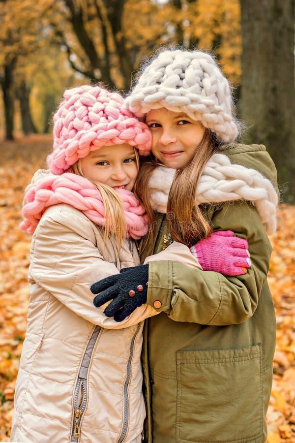 Dwa dziewczyny ściska w parkowej kapeluszy i scarves dzianinie szorstkiej fotografia stock