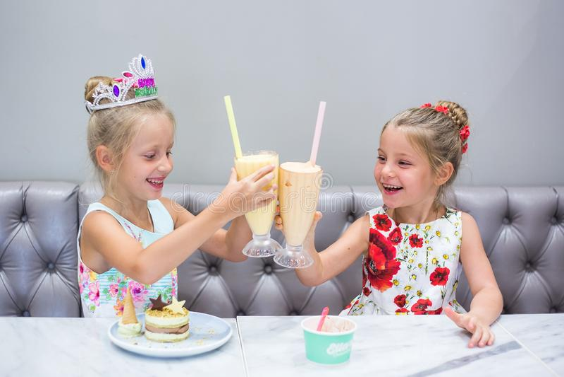 Dwa dziewczyny ?wi?tuj? ich urodziny Dziecka ` s wakacje Taktuje cukierki, tort i sok na stole, fotografia royalty free
