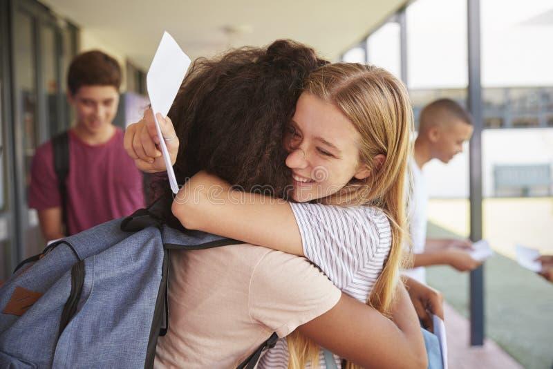 Dwa dziewczyny świętuje egzamin wynikają w szkolnym korytarzu obraz stock