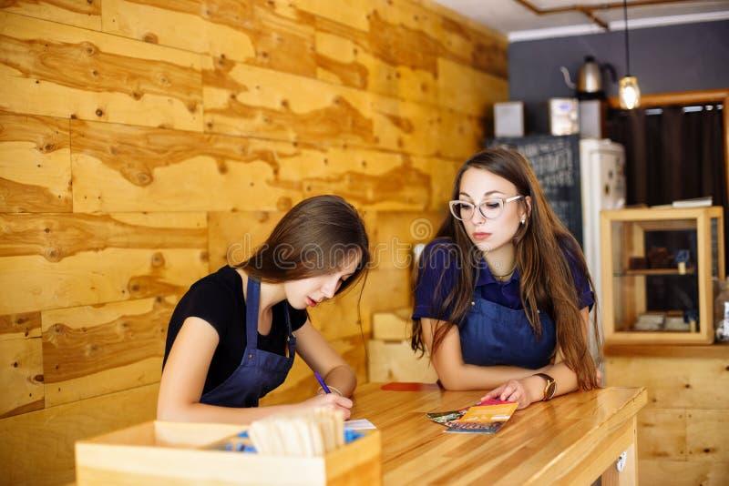 Dwa dziewczyny barista śliczny obsiadanie przy drewnianym stołem w kawowym domu obrazy stock