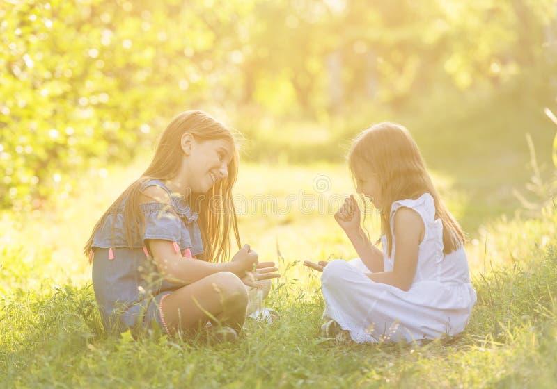 Dwa dziewczyny bawić się skała nożyc papierową grę outdoors obrazy stock