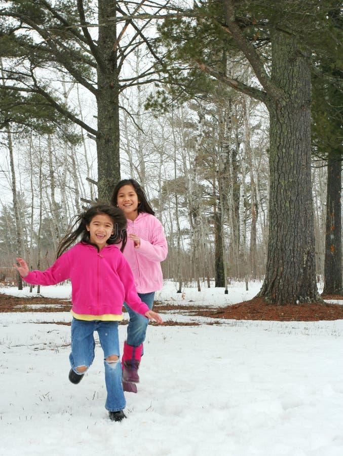 Dwa dziewczyny biega przez śniegu fotografia stock