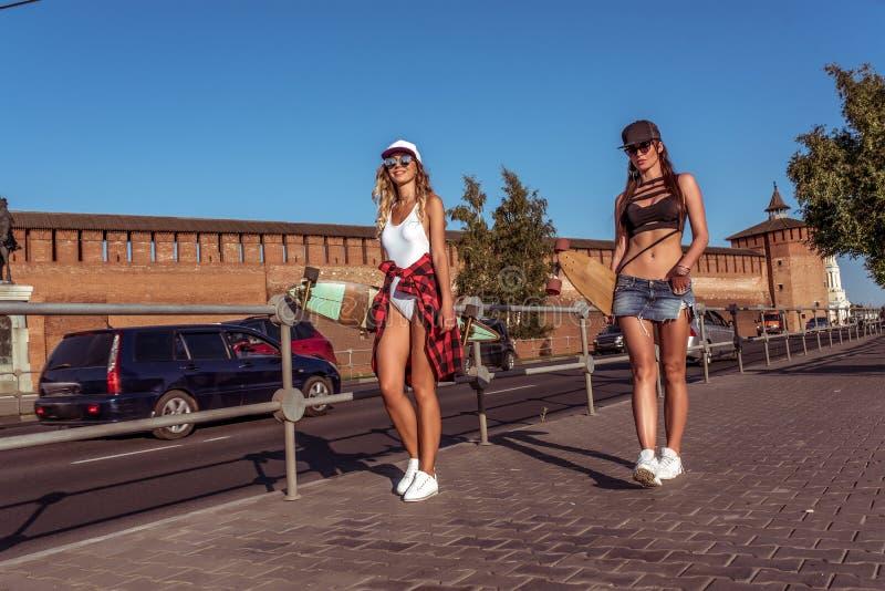 Dwa dziewczyny dziewczyny chodzi miasto, postacie, tło drogowego bruku deskorolka samochodów, pięknych i garbnikującego, Pojęcie  fotografia stock