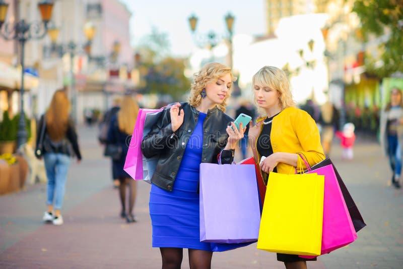 Dwa dziewczyny chodzi w dół ulicę z torbami na zakupy i patrzeje w telefon, uśmiechnięty fotografia royalty free