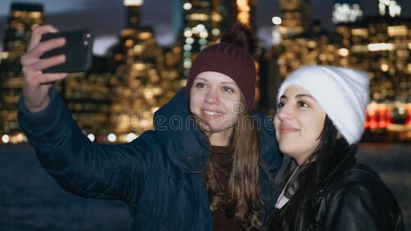 Dwa dziewczyny cieszą się cudowną noc w Nowy Jork przed Manhattan linia horyzontu zdjęcie royalty free