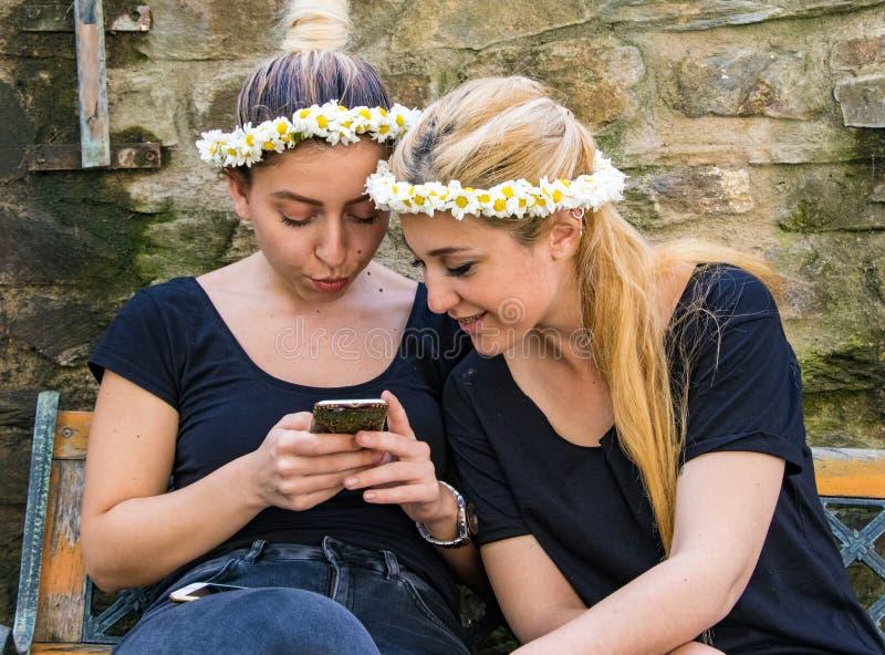 Dwa dziewczyny cieszą się patrzejący ich selfie zdjęcia royalty free