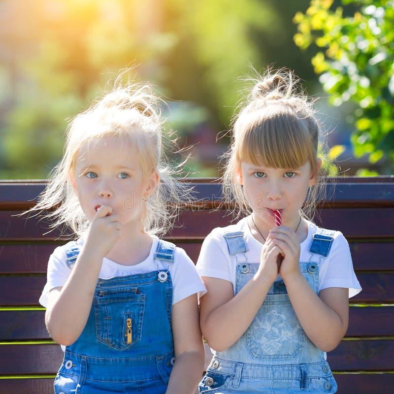 Dwa dziewczyny jedzą cukierki w parku fotografia stock