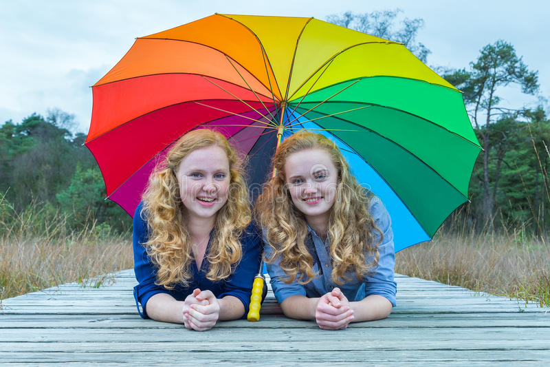 Dwa dziewczyny kłama w naturze pod kolorowym parasolem obraz royalty free