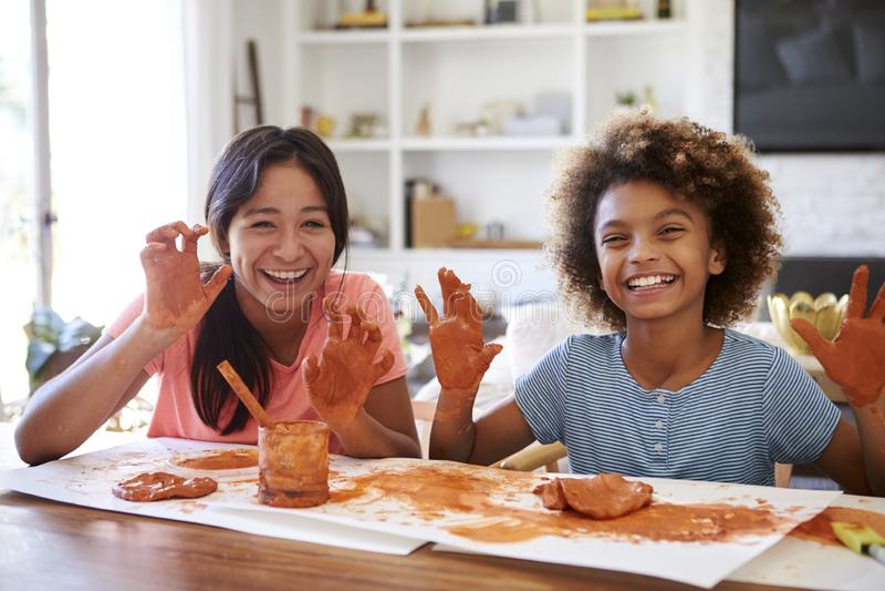Dwa dziewczyny ma zabawę bawić się z modelarską gliną w domu, uśmiecha się brudne ręki i pokazuje kamera, frontowy widok, zakończ obrazy stock