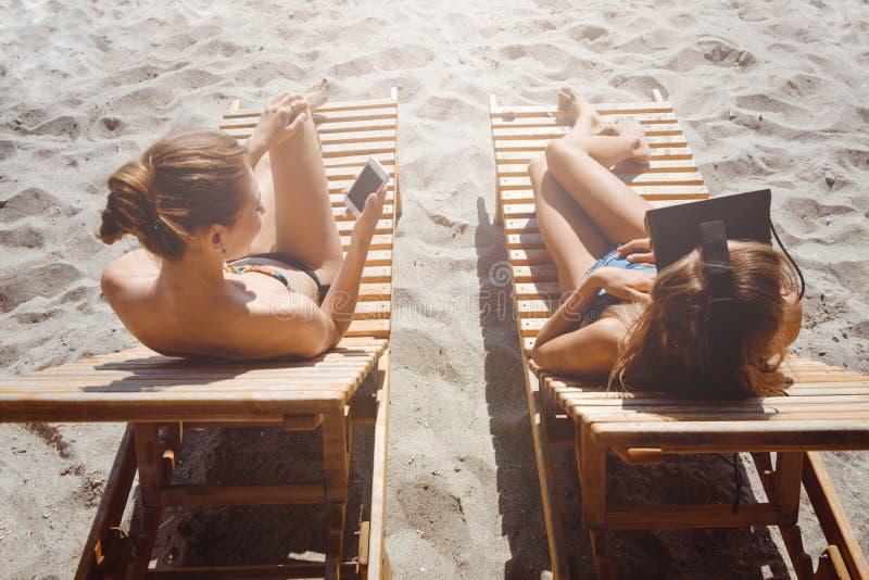 Dwa dziewczyny ma zabawę z VR smartphone na plaży i szkłami zdjęcie stock