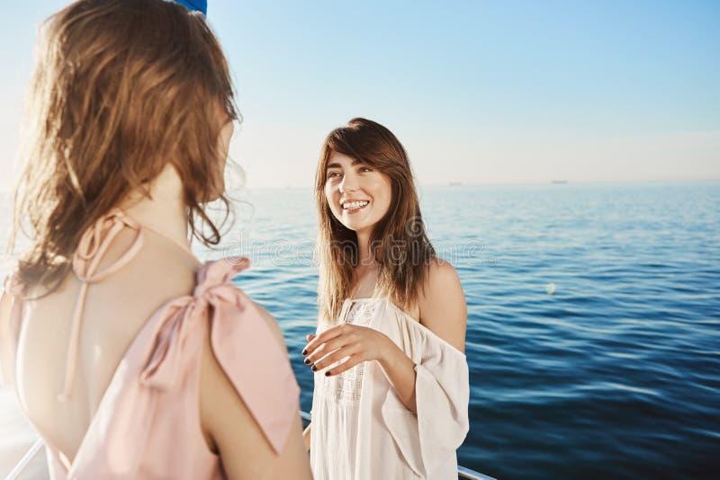 Dwa dziewczyny na jachtu żeglowaniu w morzu, mieć rozmowę o ich wielkich planach dla wakacje Szczęśliwa dorosła kobieta opowiada fotografia stock