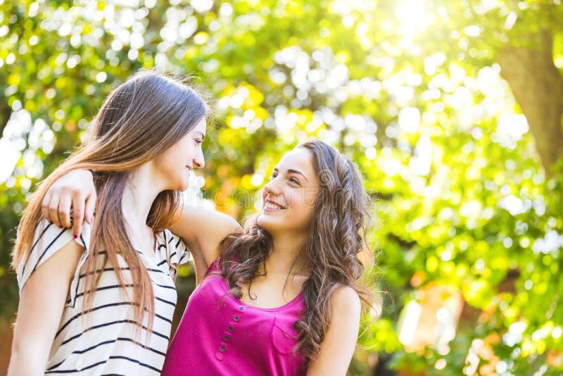 Dwa dziewczyny obejmującej wpólnie przy parkiem zdjęcia stock