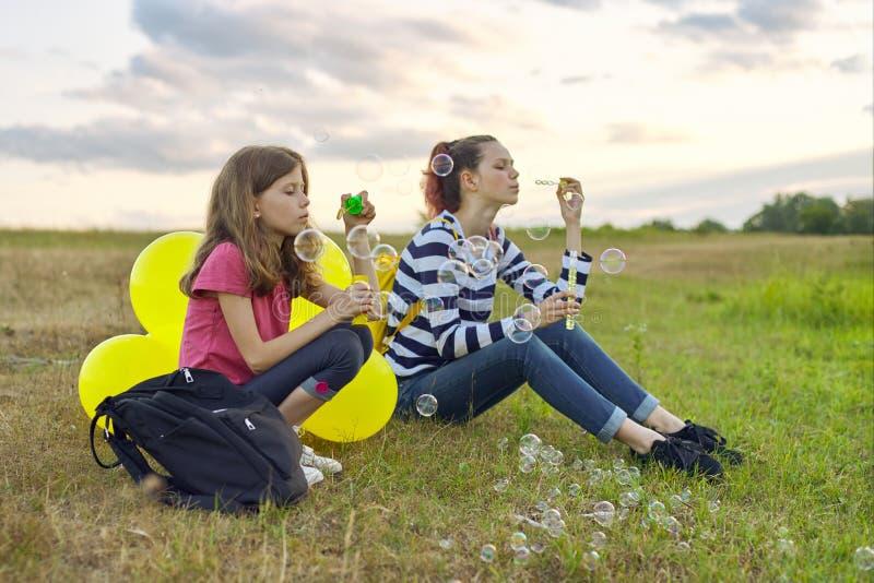 Dwa dziewczyny odpoczywa w naturze, dzieci z mydlanymi bąblami zdjęcia royalty free