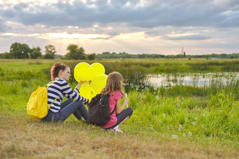 Dwa dziewczyny odpoczywa w naturze, dzieci z mydlanymi bąblami obrazy royalty free