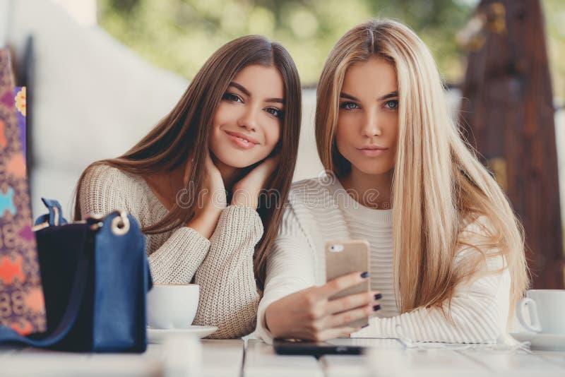 Dwa dziewczyny oglądają fotografie na smartphone zdjęcie stock