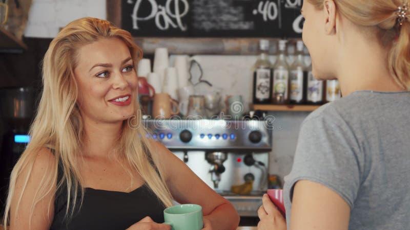 Dwa dziewczyny opowiadają przy kawiarnią zdjęcie royalty free