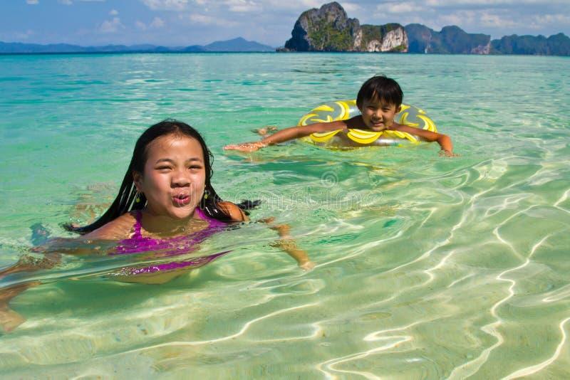 Dwa dziewczyny pływa w wodzie przy plażą zdjęcia royalty free
