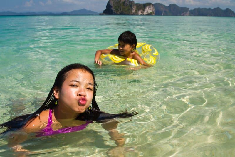 Dwa dziewczyny pływa w wodzie przy plażą obrazy royalty free