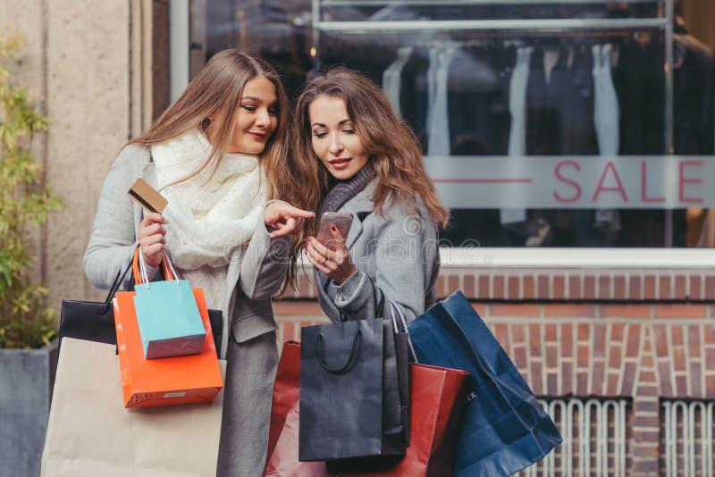 Dwa dziewczyny patrzeje mądrze telefon przed showwindow z sal obrazy royalty free