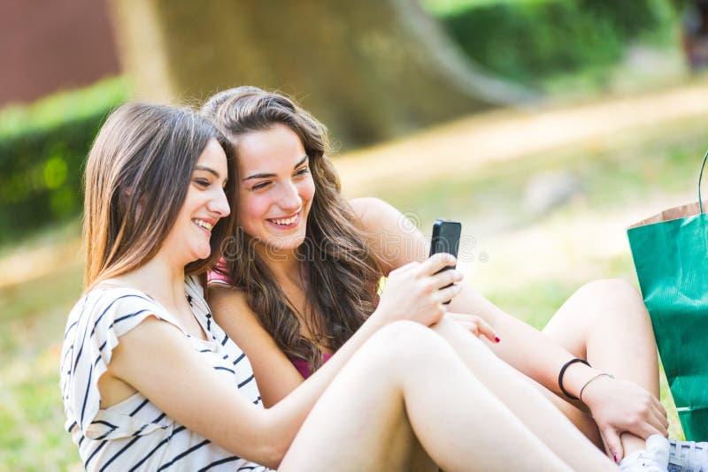 Dwa dziewczyny patrzeje mądrze telefon przy parkiem zdjęcia stock