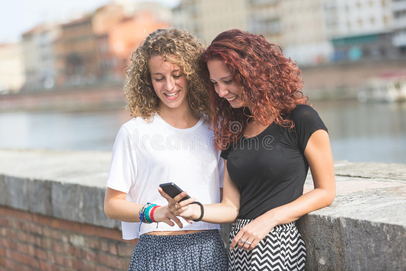 Dwa dziewczyny patrzeje mądrze telefon w mieście obrazy stock