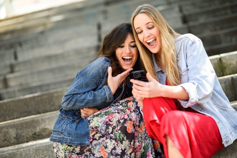 Dwa dziewczyny patrzeje niektóre śmieszną rzecz na ich mądrze telefonie fotografia stock
