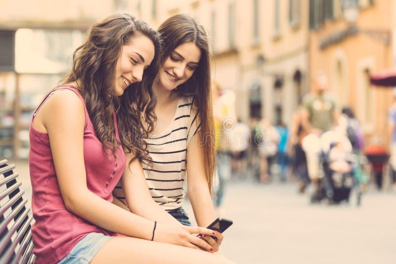 Dwa dziewczyny patrzeje smartphone obraz stock