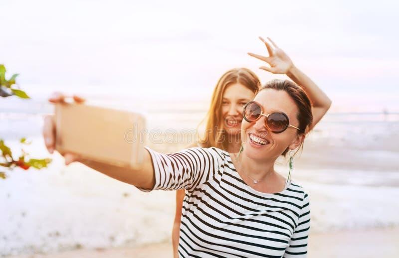 Dwa dziewczyny pozuje dla selfie na dennej stronie używa smartphone fotografia royalty free