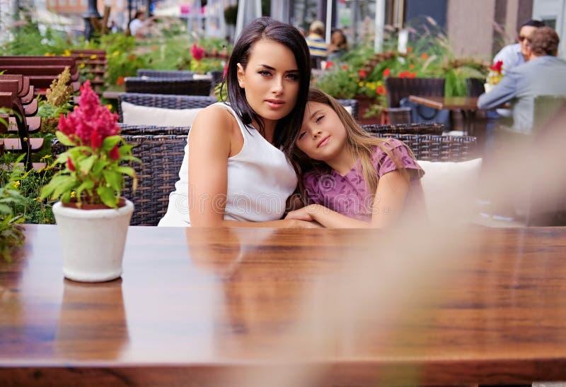 Dwa dziewczyny przy stołem w na wolnym powietrzu kawiarni obraz royalty free