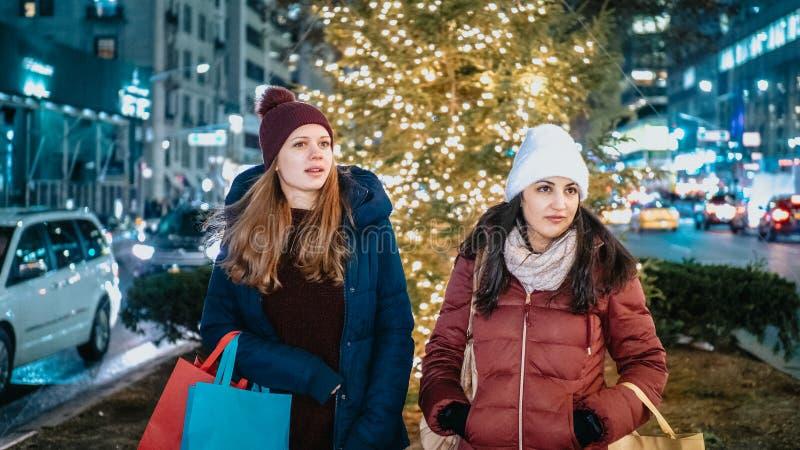 Dwa dziewczyny robią zakupy Bożenarodzeniowe teraźniejszość w Nowy Jork zdjęcie stock