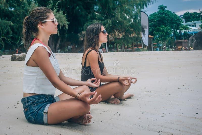 Dwa dziewczyny robi joga pozie na plaży w lotosowej pozycji zdjęcie stock