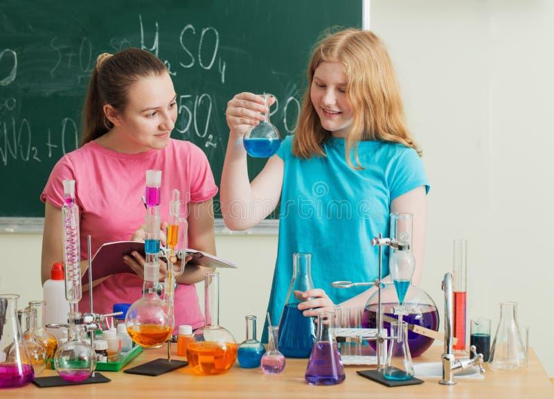 Dwa dziewczyny robi substancja chemiczna eksperymentom obraz royalty free