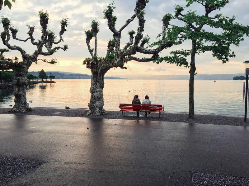 Dwa dziewczyny siedzą na czerwonej ławce na jeziorze przeciw s fotografia stock