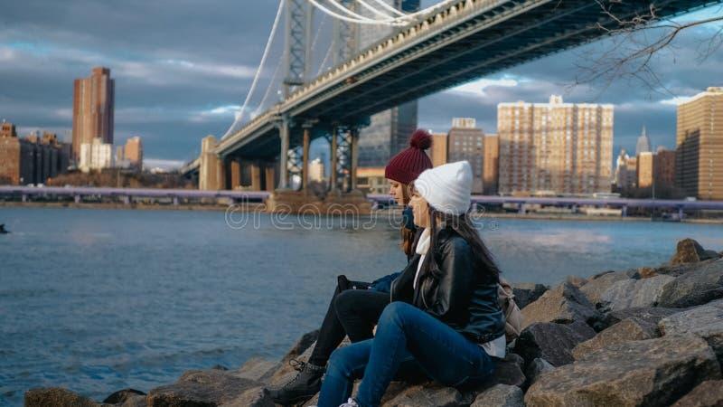 Dwa dziewczyny siedzą przy Manhattan mostem i cieszą się ich zwiedzającą wycieczkę Nowy Jork obrazy royalty free