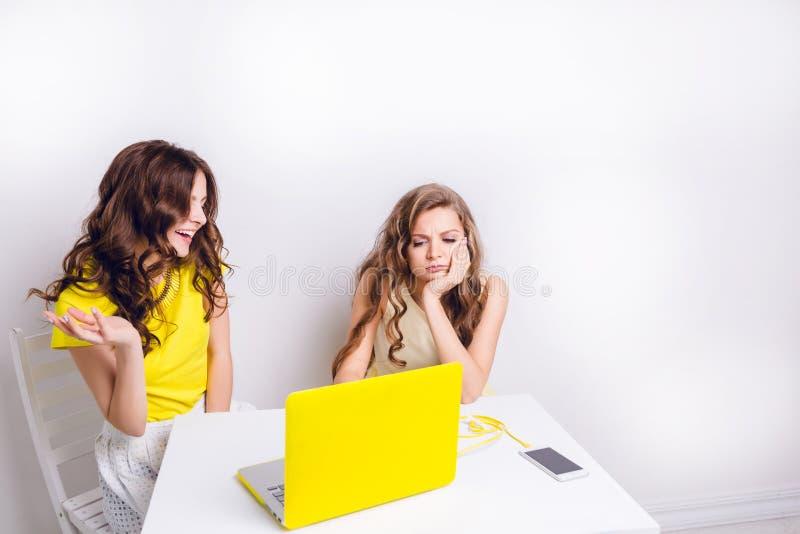 Dwa dziewczyny siedzą za laptopem w żółtej skrzynce Tam jest smartphone na stole ładuje przez koloru żółtego kabla Jeden dziewczy fotografia royalty free