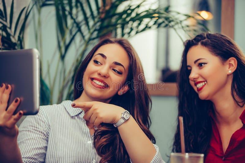Dwa dziewczyny siedzi przy stołem, używać pastylkę i dyskutują wiadomość obrazy royalty free