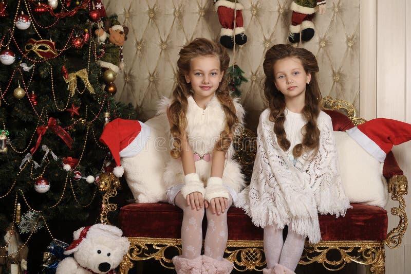 Dwa dziewczyny siostry w Bożenarodzeniowym wnętrzu zdjęcia stock