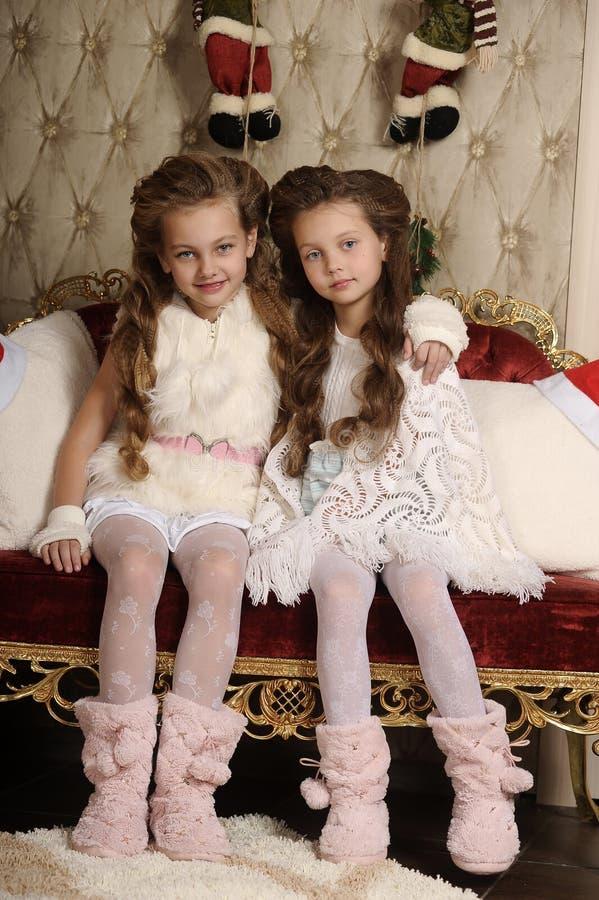 Dwa dziewczyny siostry w Bożenarodzeniowym wnętrzu zdjęcia royalty free