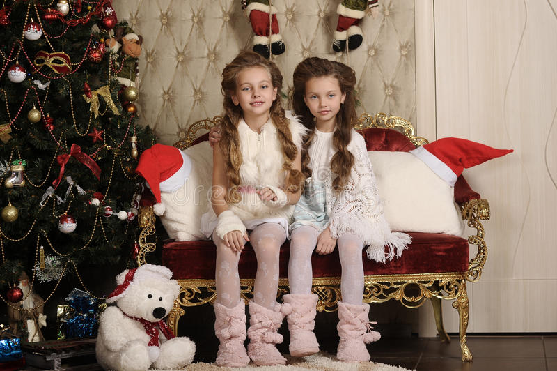 Dwa dziewczyny siostry w Bożenarodzeniowym wnętrzu obrazy royalty free