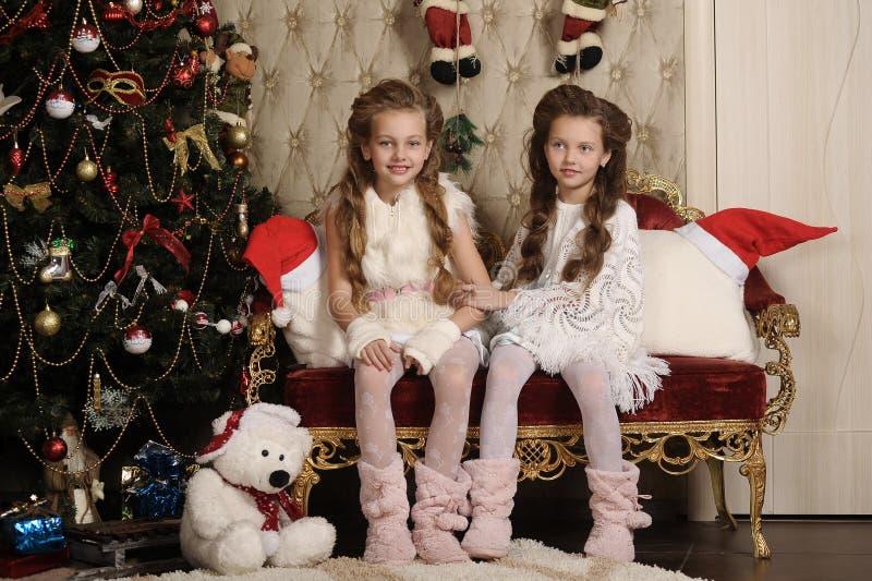 Dwa dziewczyny siostry w Bożenarodzeniowym wnętrzu zdjęcie royalty free