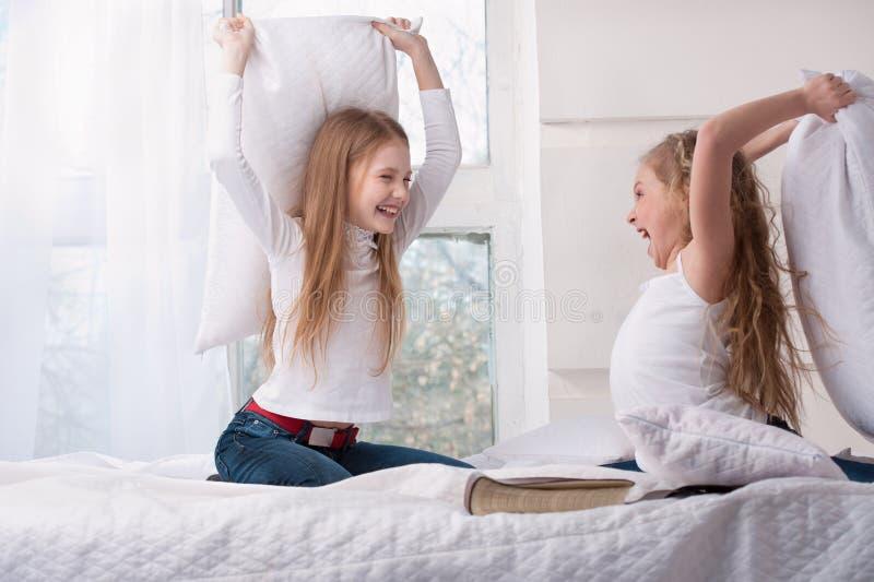 Dwa dziewczyny target698_1_ poduszki walkę w łóżku. obrazy royalty free