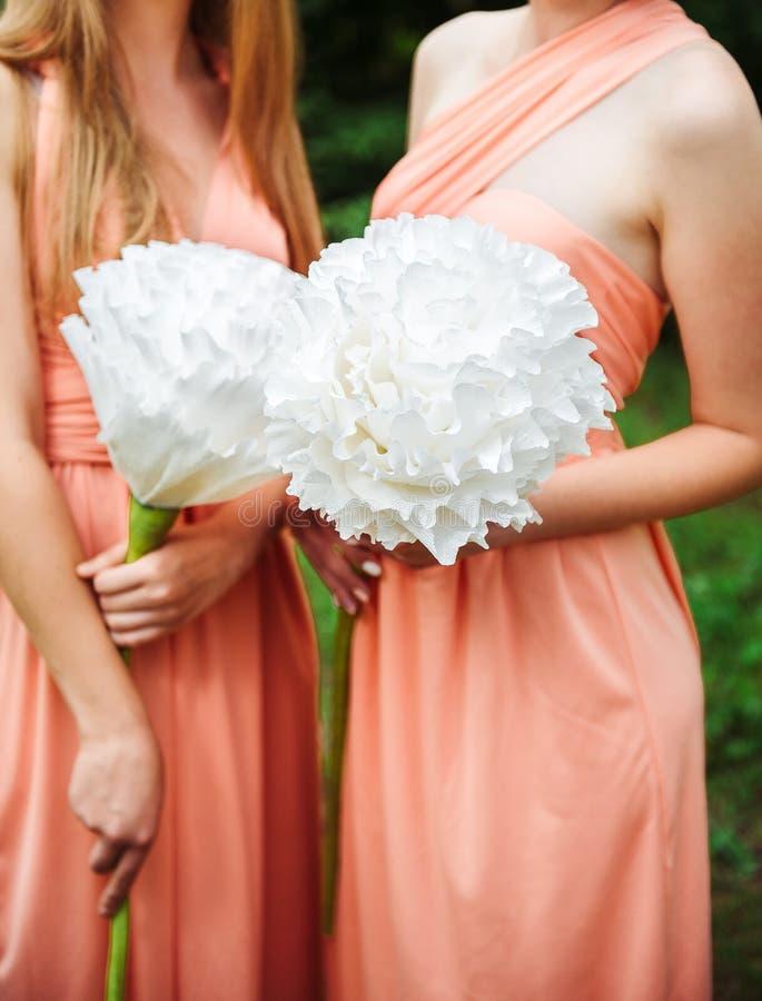 Dwa dziewczyny trzyma ogromnych papierowych białych kwiaty w sukniach zdjęcie royalty free