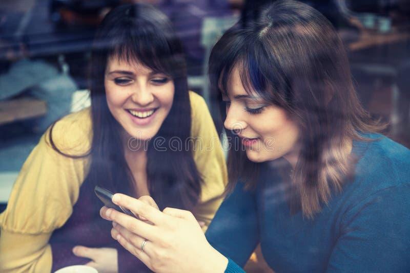Dwa dziewczyny uśmiecha się mądrze telefon i używa w kawiarni obraz royalty free